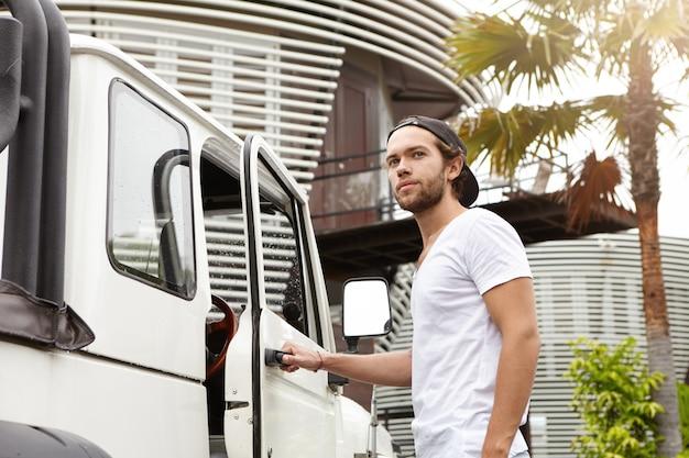 人、レジャー、ライフスタイルのコンセプトです。 tシャツと野球帽をかぶった屋外でポーズをとるファッショナブルな若い男性モデル