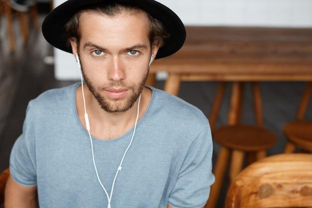 Люди, досуг и образ жизни. крытый портрет модного молодого бородатого студента в стильной шляпе, смотрящего, отдыхающего в кафе