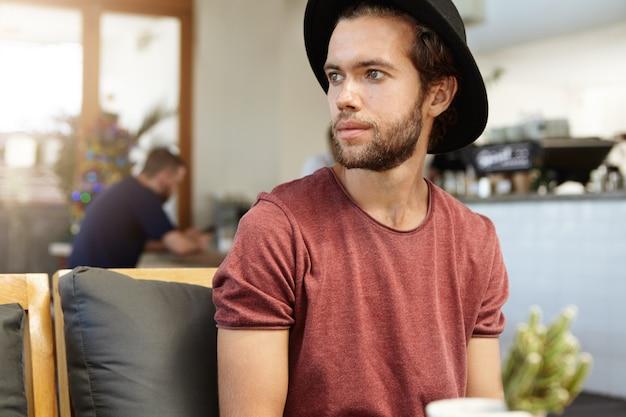 사람, 레저 및 현대적인 라이프 스타일 개념. 실내에서 혼자 휴식을 갖는 검은 모자를 쓰고 두꺼운 수염을 가진 잘 생긴 젊은 남자의 초상