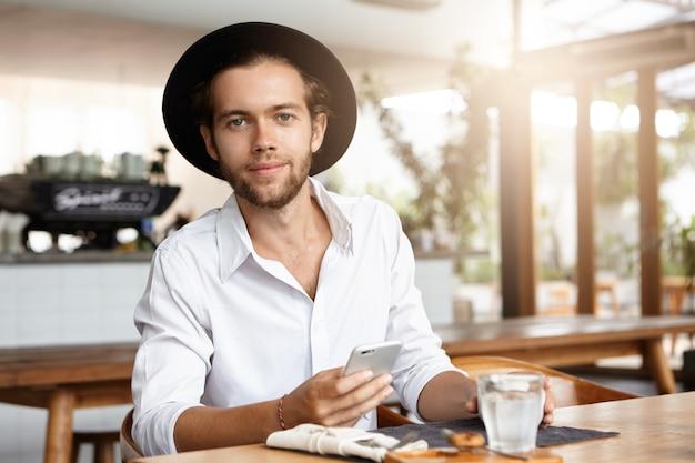 人、レジャー、そして現代のテクノロジー。彼のスマートフォンで高速インターネット接続を楽しんで幸せそうな顔つきの若い学生。カフェで電子デバイスを使用してトレンディな帽子のファッショナブルな男