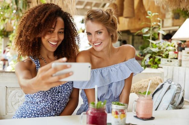 人、レジャー、レクリエーションの時間。陽気なアフリカ系アメリカ人女性と彼女の親友はカフェで自由な時間を過ごし、携帯電話で自撮りを作って、スムージーを飲みます。多民族の関係の概念
