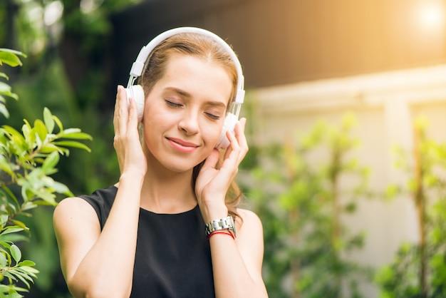 사람들이 레저 및 기술 개념-야외에서 음악 플레이어에서 음악을 듣고 매력적인 젊은 여자. 아침 공원에서 그녀의 이어폰에서 음악을 즐기는 hipster 소녀. 렌즈 플레어.