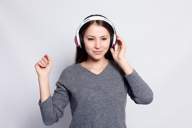 人々、レジャー、テクノロジーのコンセプト-スマートフォンから音楽を聴いて踊るヘッドフォンで幸せな女性または10代の少女