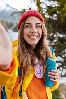 人、レジャー、旅行のコンセプト。幸せな若いヨーロッパの女性は歯を見せる笑顔を持っています