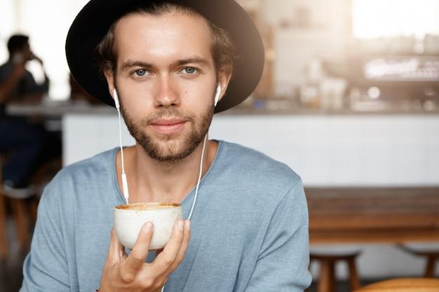 Concetto di persone e tempo libero. primo piano del volto di attraente giovane hipster in nero alla moda bere caffè e ascoltare musica