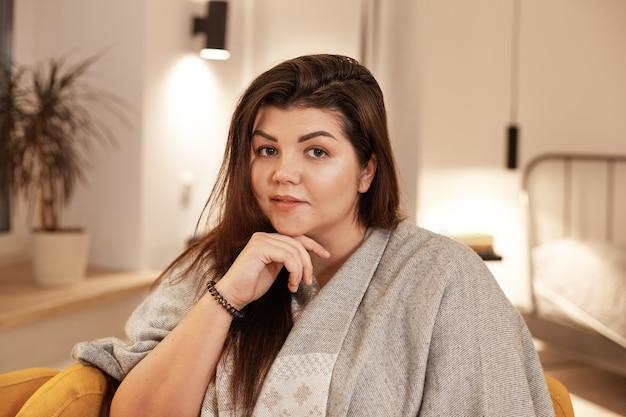 사람, 레저, 아늑함 및 라이프 스타일 개념. 따뜻한 담요에 싸여 안락 의자에 앉아 집에서 편안한 느슨한 검은 머리를 가진 매력적인 귀여운 젊은 더하기 크기 여성의 실내 이미지