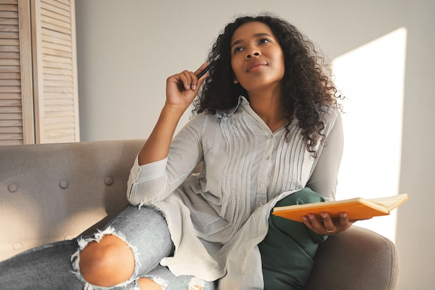 People, leisure and creativity concept. picture of successful beautiful young african self employed woman looking up with deep in thoughts facial expression while making notes in her diary