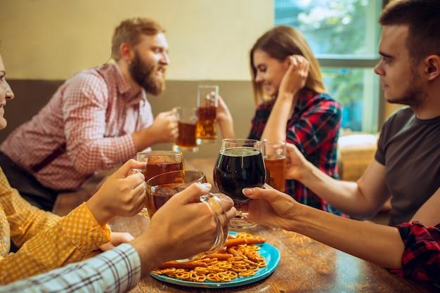 人、レジャー、友情、コミュニケーションのコンセプト。ビールを飲んだり、バーやパブでグラスをしゃべったり、チャリンという音を立てたり、携帯電話で自分撮り写真を作ったりする幸せな友達。