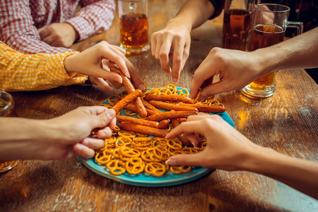 Люди, досуг, дружба и общение концепции. счастливые друзья пьют пиво, разговаривают и чокаются в баре или пабе.