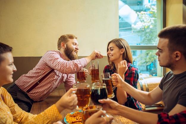 人、レジャー、友情、コミュニケーションコンセプト-ビールを飲みながら幸せな友達がバーやパブで話してチャリンというグラス