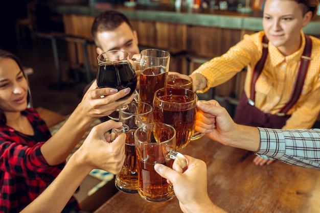 사람, 레저, 우정 및 통신 개념-맥주를 마시는 행복 친구, 얘기하고 술집이나 술집에서 안경을 부딪 치는