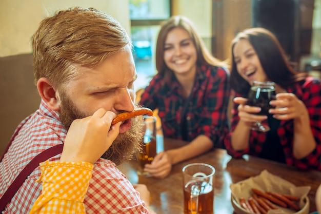 人、レジャー、友情、コミュニケーションコンセプト-ビールを飲みながら幸せな友達が話しているとバーやパブでグラスをチャリンという音
