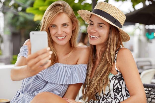 人、レジャー、ライフスタイル、近代的な技術の概念。 2つの幸せなレズビアンは屋外で楽しんでいます。金髪の愛らしい女性が帽子で彼女の魅力的なガールフレンドとのselfieのための現代の携帯電話のポーズを保持しています。