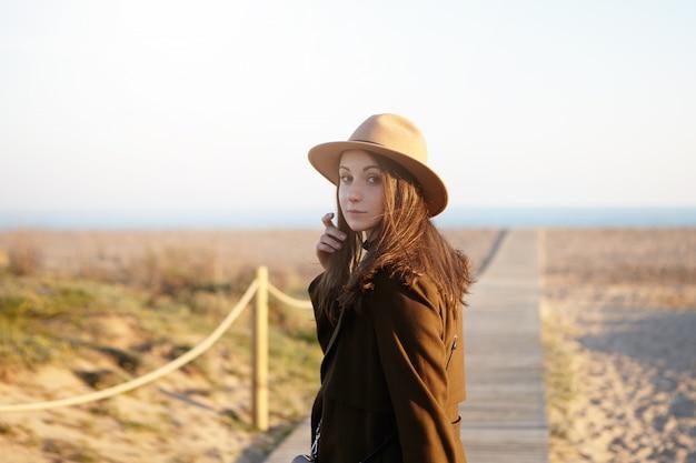 人、レジャー、ライフスタイル、旅行。海岸線を歩いて、彼女の緩んだ髪に触れて、振り向いて、海外旅行中に海に急いで幸せで屈託のないブルネットの女性