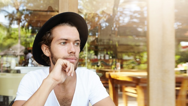 People, leisure and lifestyle concept. handsome young bearded male in headwear holding hand on his chin while relaxing at modern sidewalk cafe during lunch, waiting for waiter