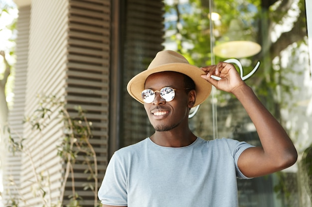 People, leisure and lifestyle concept. happy and relaxed young black european man in stylish clothing adjusting brims of his hat smiling broadly while flirting with pretty woman at sidewalk cafe