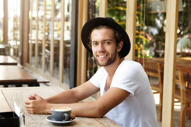People, leisure and lifestyle concept. successful young man in black hat and casual t-shirt having coffee sitting at sidewalk restaurant