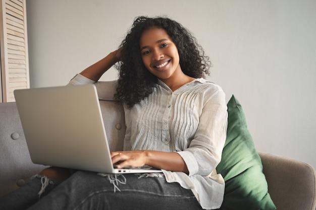 人、レジャー、現代のライフスタイル、テクノロジー、電子機器のコンセプト。オンライン通信を楽しんで、自宅でラップトップコンピューターを使用してビデオチャットを持っている魅力的な幸せな若い混血の女性