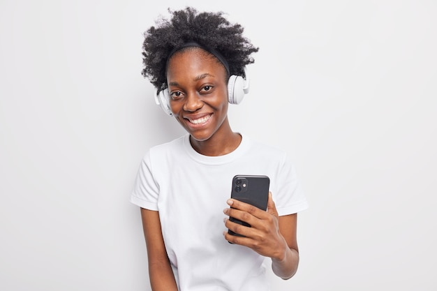 Concetto di tecnologie moderne per il tempo libero della gente. una bella donna riccia nera sorride felicemente tiene il cellulare e indossa le cuffie stereo per ascoltare la musica