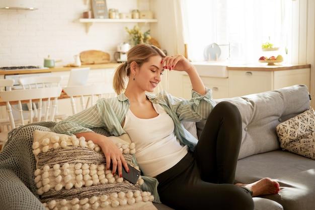 人、レジャー、現代のテクノロジーとコミュニケーションのコンセプト。カジュアルな服装の裸足の若い女性がソファに快適に座って、自宅で社会的に距離を置き、携帯電話を使用して友達とチャットします