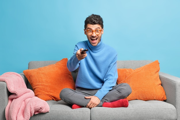 People leisure pastime concept. overjoyed unshaven adult man sits in lotus poses on sofa holds remote control and watches funny show on television
