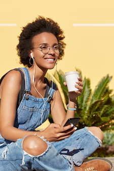 People, leisure, technology concept. teenage girl with dark skin, toothy smile, enjoys recording in earphones, listens music from playlist, entertains herself, sits crossed legs wears stylish overalls