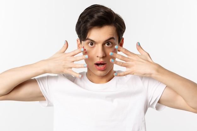 Люди, лгбт и концепция красоты. крупный план красивого гея с блеском на лице, показывая лак на ногтях, дерзко глядя в камеру, стоя на белом фоне.