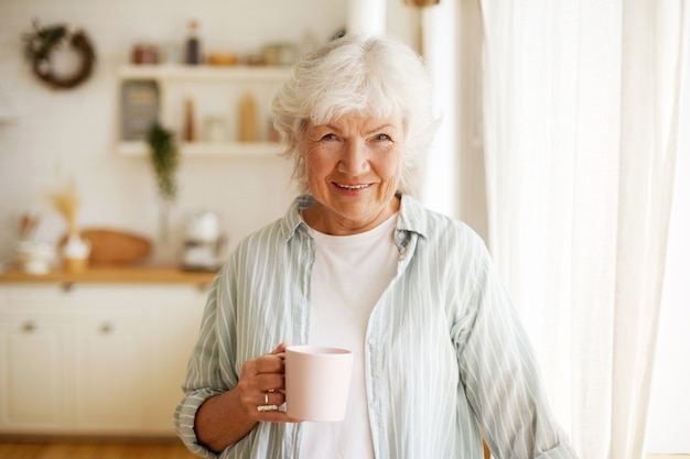人、ライフスタイル、年齢、退職。家でリラックスし、ハーブティーを飲み、広く笑っている陽気な幸せなヨーロッパの女性年金受給者のイメージを腰に当てる