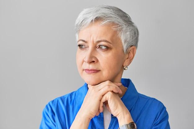人、ライフスタイル、年齢のコンセプト。灰色のピクシーヘアの深刻な白人女性年金受給者は、握りしめられた手にあごを置き、目をそらし、動揺して孤独を感じます。悲しい成熟した女性の肖像画