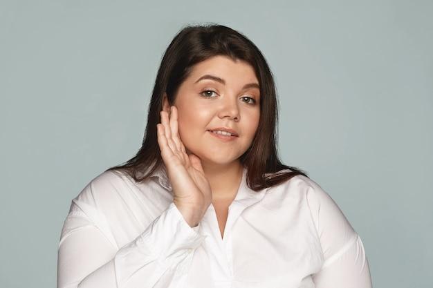 人、ライフスタイル、美容のコンセプト。光沢のある輝く肌のために仕事の前に顔に保湿剤を適用する白いシャツのかわいい魅力的な若いブルネット太りすぎの女性従業員の孤立したショット