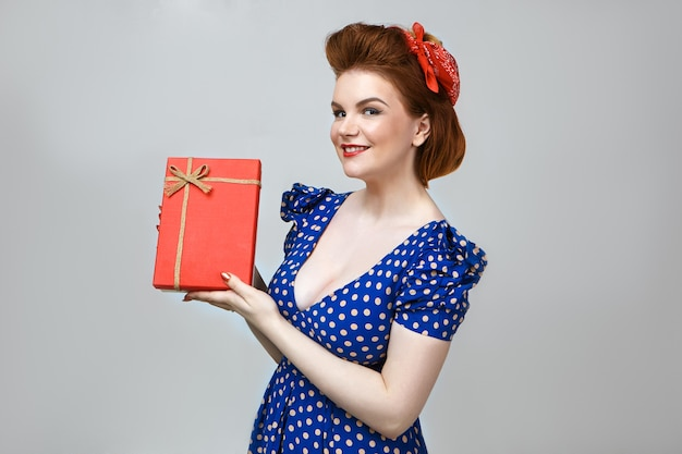 人、ライフスタイル、休日のコンセプト。幸せを感じ、赤い箱を持って、誕生日プレゼントで喜んで、スタイリッシュなヴィンテージの服を着た陽気な若いヨーロッパの主婦のスタジオショット