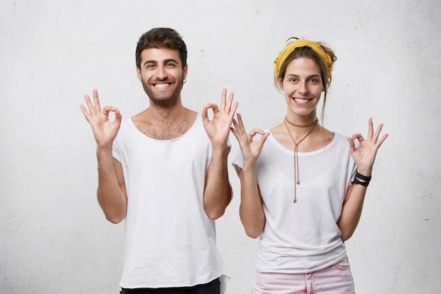 人、ライフスタイル、関係の概念。彼らが素晴らしい、うれしいことを示している、大丈夫なジェスチャーでポーズをとって幸せな若い白人カップルの肖像画