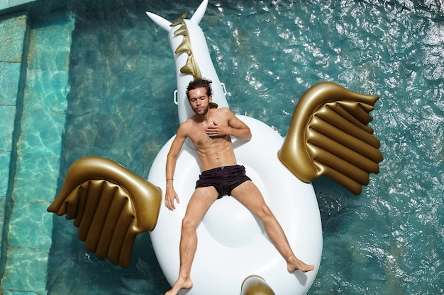 사람, 라이프 스타일, 여름 휴가 개념. 행복하고 평온한 날을 즐기고, 팽창 식 매트리스에 떠있는 야외 수영장에서 편안한 검은 색 수영 팬티를 입고 자신감있는 매력적인 남성