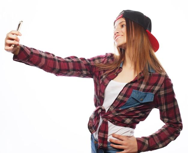 人々、ライフスタイル、技術の概念:帽子をかぶって、スマートフォンで自分撮りをしているかわいい十代の少女-白で隔離
