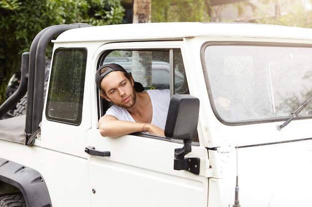 人、ライフスタイル、観光の概念。サファリの冒険旅行中に野生の自然を楽しんでいる彼の白い車を運転してスナップバックを着ているハンサムな若い男性の観光客
