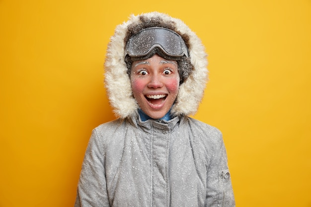 사람들의 라이프 스타일과 겨울 활동 개념. 밝고 어두운 피부를 가진 여성의 미소는 겨울 재킷과 스키 고글을 착용하고 hapiness로 가득 차 있습니다.
