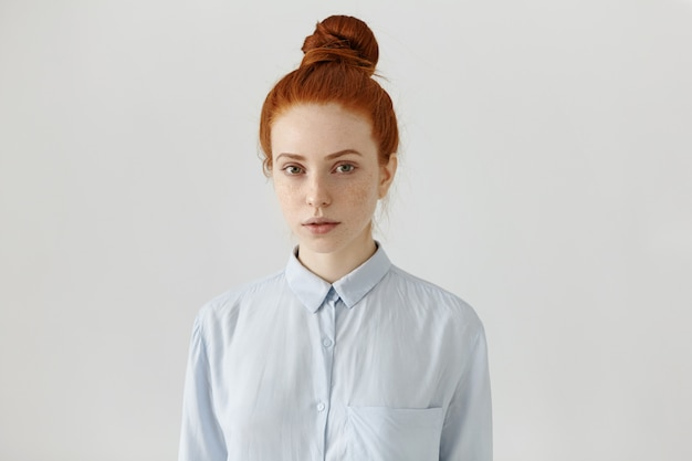 People and lifestyle. attractive european student woman with freckles and ginger hair in bun wearing formal shirt, ready for college