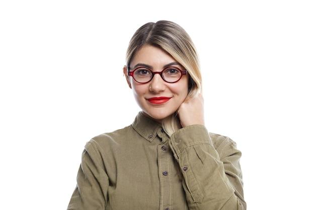 人、ライフスタイル、美しさ、ファッション、スタイル。トレンディな眼鏡、赤い口紅、スタイリッシュなシャツを着て、幸せな興奮した表情で白い壁にポーズをとるファッショナブルな若いヨーロッパの女性
