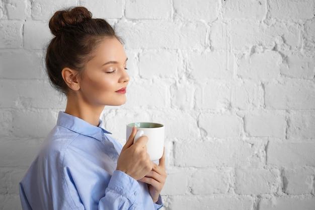 人、ライフスタイル、飲み物、食べ物、休息、リラクゼーションのコンセプト。目を閉じて朝のコーヒーを楽しんで、カップを保持しているスタイリッシュなフォーマルシャツで美しいゴージャスな若い女性マネージャーの屋内ショット