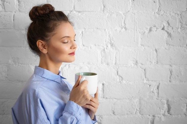 People, lifestyle, beverage, food, rest and relaxation concept. indoor shot of beautiful gorgeous young female manager in stylish formal shirt holding cup, enjoying morning coffee with eyes closed