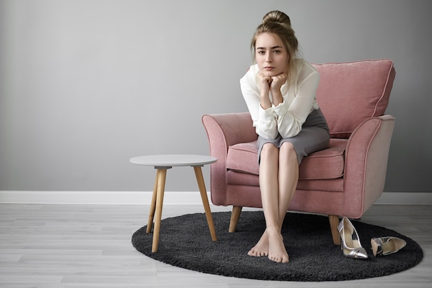 People and lifestyle concept. beautiful young female teacher with hair bun relaxing at home after lectures at college, sitting barefooted in armchair, looking at camera with tired facial expression