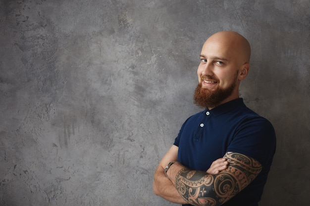 People and lifestyle concept. handsome confident young bearded european man having sly smile, crossing arms on his chest, standing at wall with copyspace for your promotional content