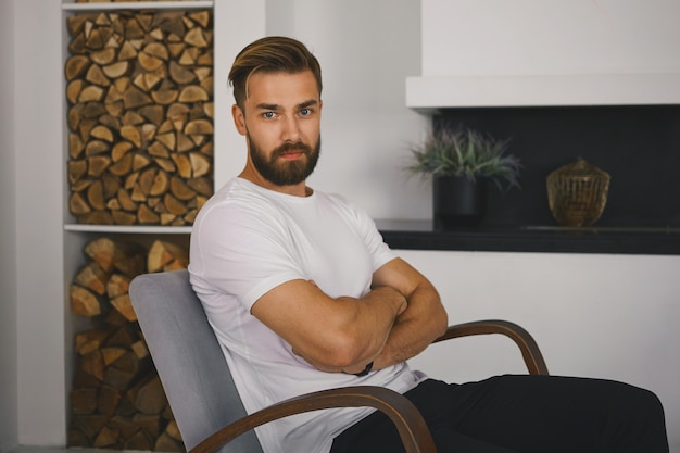 People and lifestyle concept. horizontal shot of handsome unshaven young european male with athletic body and hairy face relaxing at home, keeping his arms folded, having serious expression