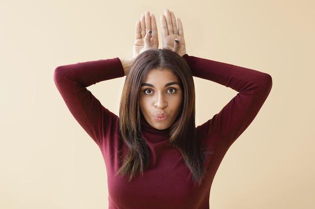 Persone e concetto di stile di vita. foto di divertente giovane signora afroamericana in collo di tartaruga viola scherzare in casa, labbra imbronciate e tenendo entrambe le mani dietro la testa come orecchie di coniglio