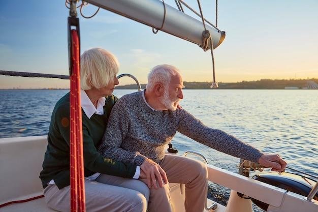 ヨットやヨットのデッキに座っている人々のライフスタイルの概念シニアカップル老人と女性