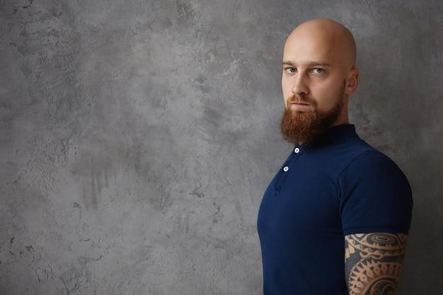 Persone e concetto di stile di vita. mezzo busto immagine di attraente alla moda giovane europeo con la barba lunga maschio con testa calva ed elegante barba allo zenzero avente una brutta giornata,