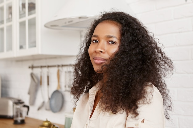 人、ライフスタイル、料理、食べ物のコンセプト。仕事から夫を待っている巻き毛のかわいいスタイリッシュな若い暗い肌の主婦の屋内ショット、キッチンで夕食を作りに行く、見て