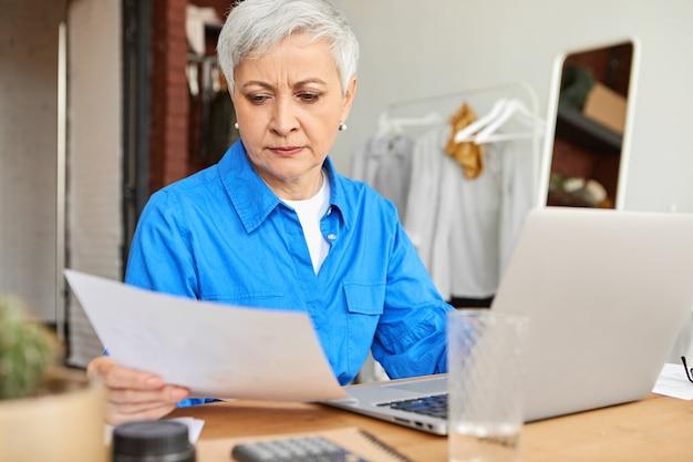 人、ライフスタイル、家庭性、そして現代のテクノロジーコンセプト。ノートパソコンと電卓を使用して自宅で家計をしている、紙のシートを保持している短い白髪の集中した引退した女性