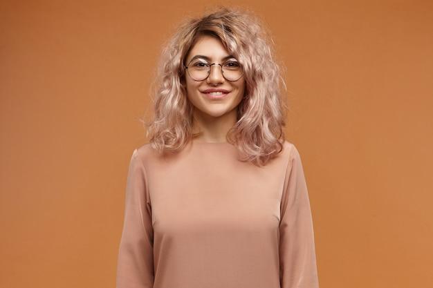 人、ライフスタイル、ファッション、光学のコンセプト。ボリュームのある髪と前向きな感情を表現する陽気なフレンドリーな笑顔を持つ魅力的な愛らしいヨーロッパのヒップスターの女の子