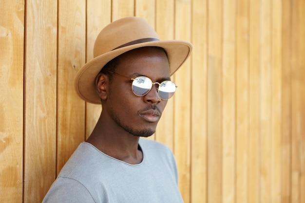 Concetto di persone, stile di vita e moda. ritratto di giovane modello maschio afroamericano alla moda bello che indossa le tonalità e il cappello d'avanguardia, nascondendosi dal sole nell'ombra, appoggiandosi contro la parete di legno